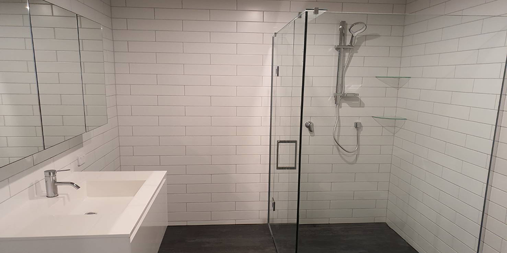 White and black bathroom with a sink and shower